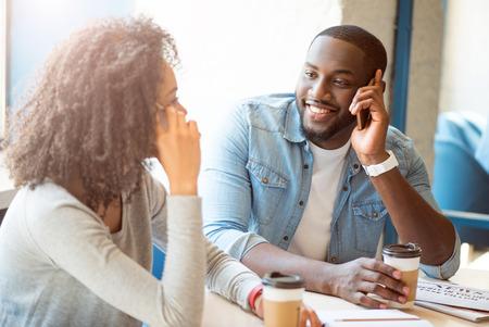 Wees altijd bereikbaar. Glimlachende en gelukkige moderne jonge mensen die in een cafe zitten en koffie drinken terwijl ze op hun mobiele telefoons praten