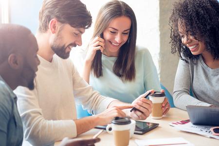 분위기를 만끽. 현대 젊은 사람들이 카페에 앉아 자신의 휴대 전화 및 디지털 태블릿을 사용하는 동안 커피를 마시고 자신의 자유 시간을 즐기는 긍정