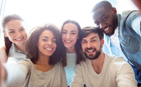Voor altijd vrienden. Positief en vrolijk moderne jonge mensen bij elkaar zitten en het nemen van een foto selfie terwijl ze in een vriendelijke stemming