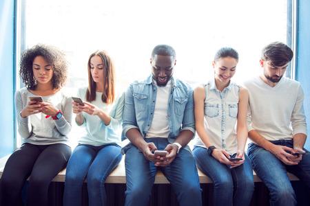 최신 레저까지. 문자 메시지를 창틀에 앉아 입력하는 동안 자신의 휴대 전화를 사용하는 젊은 사람들의 긍정적이고 명랑한 그룹
