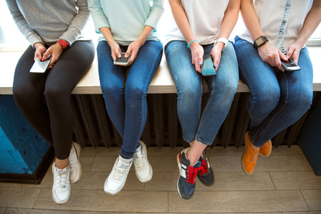 L'utilisation des téléphones mobiles. image recadrée de quatre jeunes femmes modernes en utilisant leurs téléphones mobiles tout en restant assis sur un rebord de fenêtre Banque d'images - 57933473