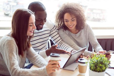 Colegas amistosos. Gente joven alegre y sonriente sentados juntos en un café y tomando café mientras usa una tableta digital y un teléfono inteligente y comunicando