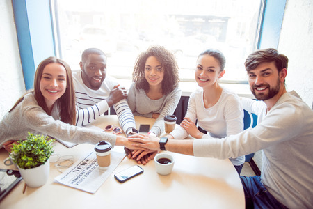 atmosphere: Being one united team. Smiling and positive young people sitting together in an informal atmosphere while drinking coffee and using various devices