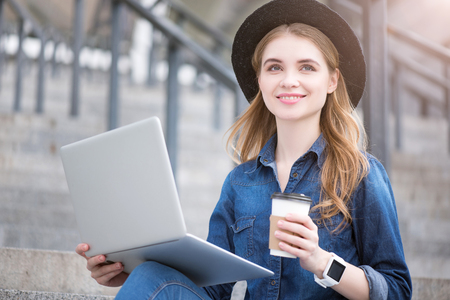 wistful: Planning future. Wistful and smiling dreamy young woman using a laptop while being outside and drinking coffee