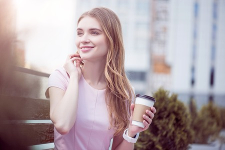 Being reachable. Smiling and content young woman talking on a smartphone and drinking coffee while being outdoors and sitting on a wooden bench