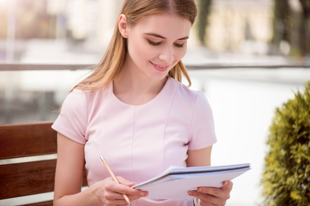 noting: Business notes. Smiling and confident young businesswoman holding a copybook and a pencil while sitting on a wooden bench and noting something