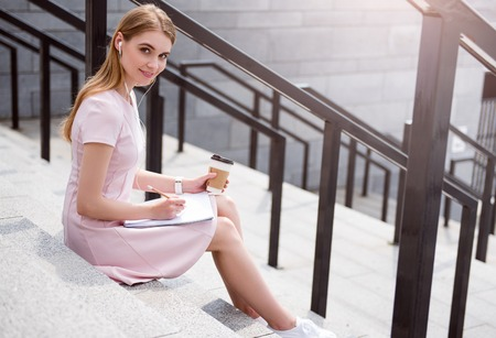 noting: Working outdoors. Smiling and content young woman listening to music using headphones while sitting on the stairs, noting something in her copybook and drinking coffee