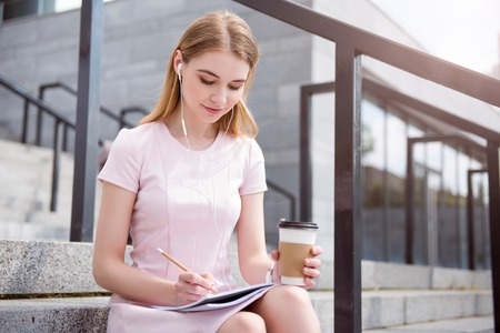 noting: Work and relax. Cheerful and confident young woman listening to music using headphones while sitting on the stairs, noting something in her copybook and drinking coffee