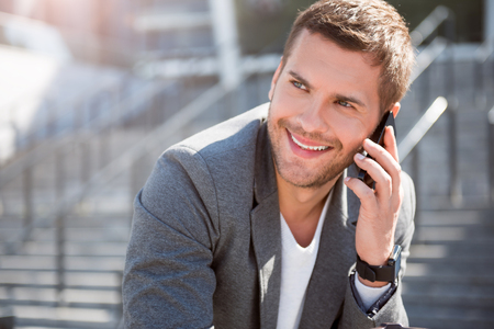 hear business call: Per phone. Smiling and positive young businessman talking on a smartphone and being in a very good mood Stock Photo