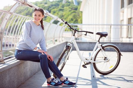 bicycle walk: In a good mood. Charming young woman sitting on a border near her bicycle after a good walk and looking at the camera