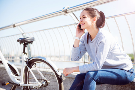 i am here: I am here. Smiling happy young woman talking on her smartphone while sitting near a bike Stock Photo