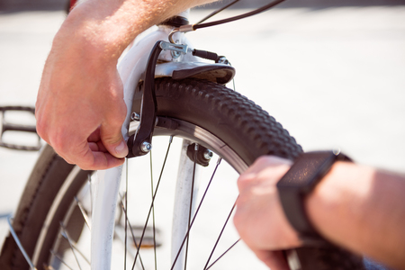 contended: Last checking. Picture of hands of a man checking a wheel of his bicycle before riding