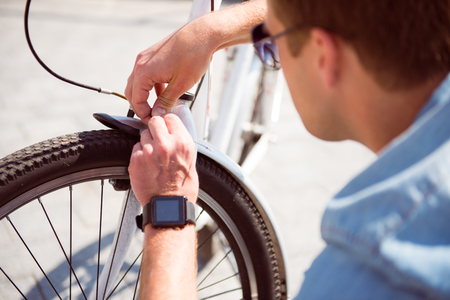 contended: I have to do it. Young man with sunglasses repairing attentively a handbrake on his bicycle