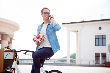 contended: Waiting for you. Contended smiling young man talking on the phone while sitting on the bike and holding flowers