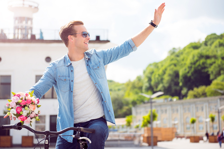 salutation: I am here. Cheerful young man with sunglasses sitting on a bike and waving a hand in sign of salutation while holding flowers