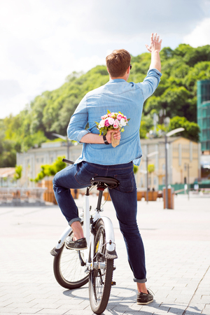 salutation: Making a surprise. Handsome young man holding flowers behind his back and waving a hand in sign of salutation while sitting on a bike