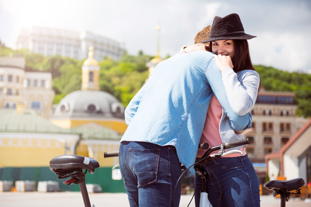 contended: So good. Contended young woman hugging a man while standing with bicycles and looking at the camera