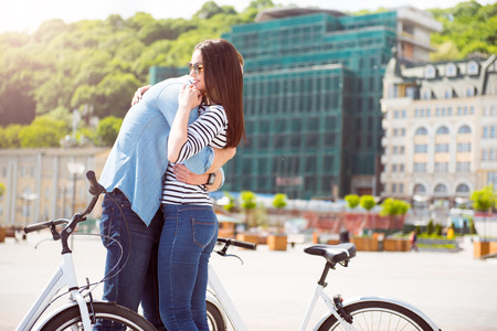 Mi sei mancato. Handsome uomo alto che abbraccia una piacevole giovane donna con occhiali da sole in piedi con le bici