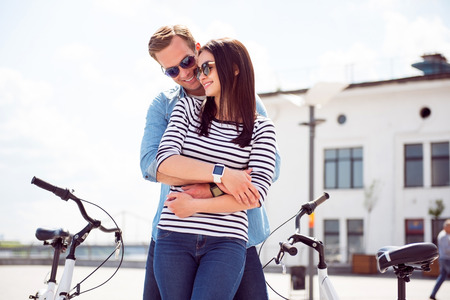 contended: Nice meeting. Contended young man hugging back a pretty young woman with sunglasses while standing near bikes Stock Photo