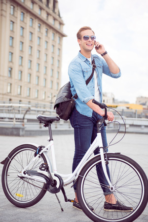 contended: Yes I am here. Contended smiling young man talking on the phone while standing near a bicycle