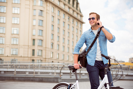 contended: Waiting for you. Cheerful smiling young man talking on the phone while standing near a bicycle Stock Photo