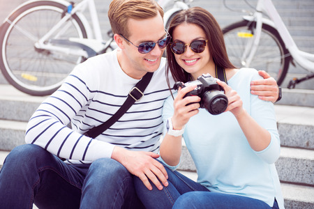 contented: Nice shot. Happy young woman in sunglasses showing photos on the camera to a contented young man while sitting on the stairs