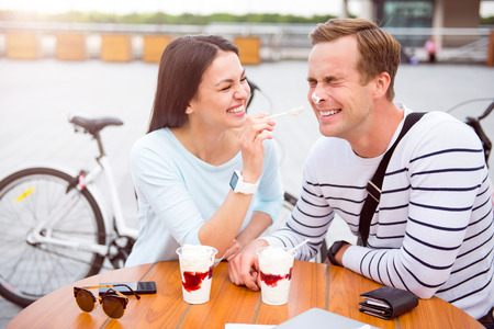 contended: Take it. Cheerful young woman laughing and touching with a spoon a nose of a funny man while sitting at the cafe Stock Photo
