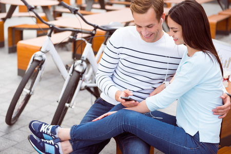 contended: Good track. Contended young woman and relaxed young man sitting and listening to music on the smartphone after riding Stock Photo