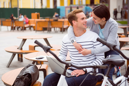 contended: Time together. Contended young woman hugging a relaxed man with a laptop and looking at him after a walk on bikes
