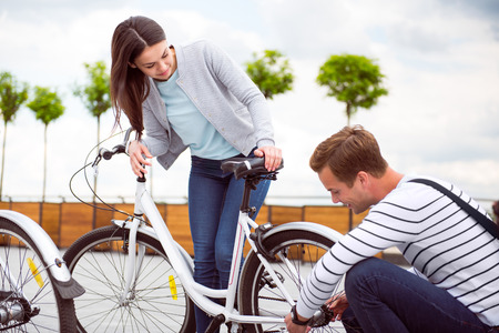 big deal: It is not a big deal. Young pensive man fixing a bicycle for a charming woman Stock Photo