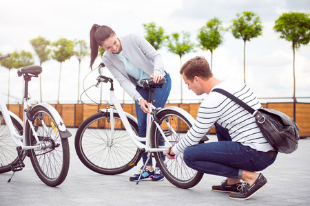 acquaintance: Be careful. Handsome pensive man fixing a wheel of a bicycle for a charming woman in the city Stock Photo