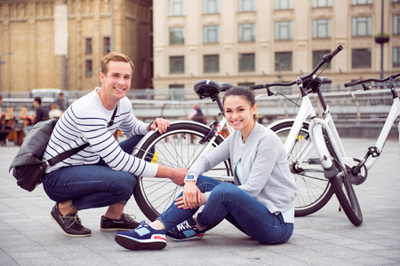 pleased: Feeling pleased. Smiling young couple sitting near the bikes with happy faces and posing for the photo