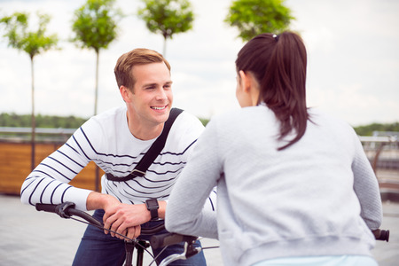 warmness: Eyes full of affection. Smiling handsome man looking at girl while leaning on his bike Stock Photo