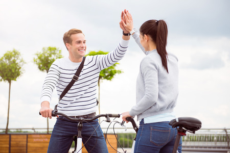 contended: Give me five. Contended young man giving five to lovely young woman while sitting on the bikes Stock Photo