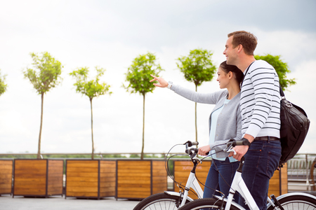 the passing of time: Passing time together. Young beautiful couple walking together with bikes on the square Stock Photo
