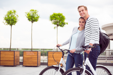 We are happy. Smiling young couple hugging and standing with bikes on the quay in the city