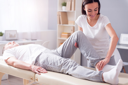 Exercise. Cheerful male patient lying down with female smiling physiotherapist performing some stretch exercises on mans leg Stock Photo
