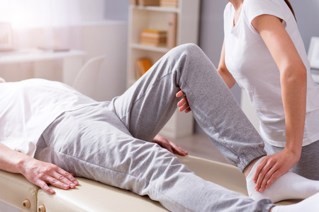 Treatment. Cropped image of male patient lying down with female physiotherapist performing some stretch exercises on mans leg Stock Photo