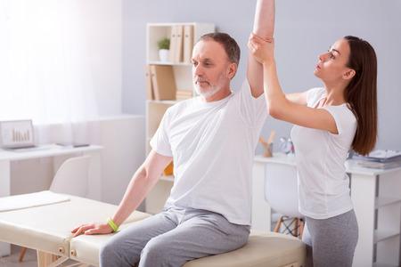 Behandeling. Vrolijke en drukke jonge vrouwelijke fysiotherapeut stretching haar mannelijke patiënt hand in een medisch kantoor