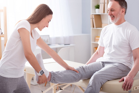 eldercare: Eldercare. Smiling and positive young female physiotherapist stretching her male patient leg in a medical office Stock Photo