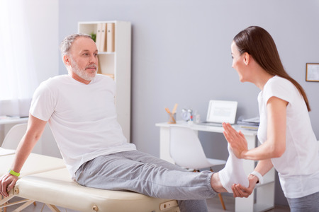eldercare: Real professional. Smiling male patient and a young female physiotherapist stretching patient foot being in a medical office