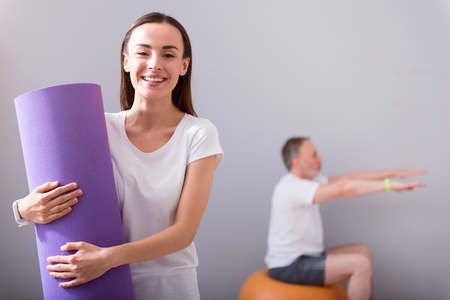 mat like: Like my job. Smiling and happy young female physiotherapist holding a mat for exercises and a male patient  sitting on a gym ball and exercising  on a background Stock Photo