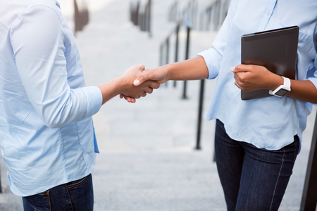 verbal: Verbal agreement. Cropped image of two business people shaking hands while holding a digital tablet Stock Photo