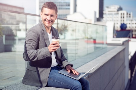 feeling positive: Feeling good. Positive and happy young man being outdoors and using his laptop while drinking coffee and smiling at a camera