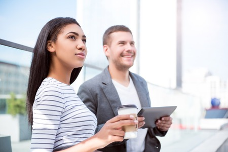 personal digital assistant: Direction. Cheerful and delighted pair of two young people holding a digital tablet while looking in one direction and drinking coffee