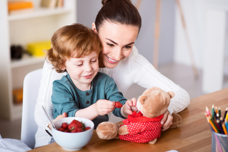 heed: I like playing with my teddy. Young cheerful mother and her funny little son feeding strawberry to the teddy bear while sitting at the table