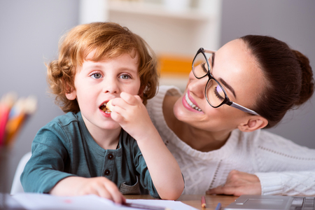contended: One more piace. Little cute calm boy eating a piece of cake while his smiling beautiful mother looking at him Stock Photo