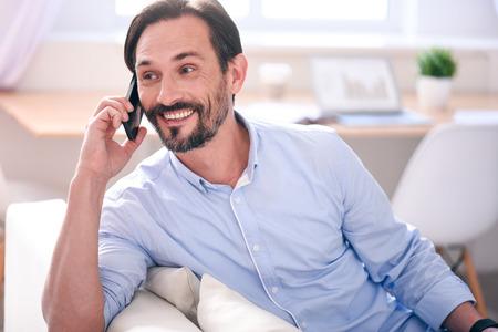 hombre con barba: Feliz de oír. Emocionado hombre de mediana edad que tiene una conversación por teléfono mientras se está sentado cómodamente en el sofá Foto de archivo