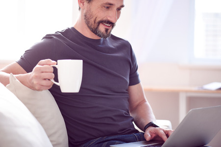 communicative: Pleasant time. Relaxed jovial man holding a cup and sitting on the sofa while working on his laptop
