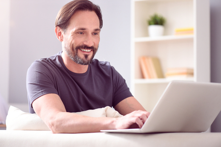 to be pleasant: So easy to be in touch. Pleasant good looking mature man looking at the screen of his laptop while sitting on the couch